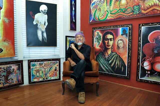 Mario Torero poses with his paintings