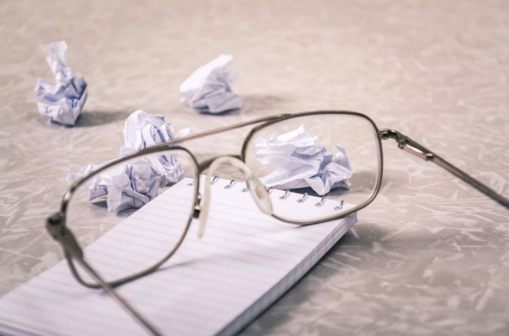 Glasses resting on a pad of paper.